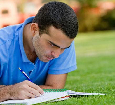 סטודנט כותב על הדשא במחברת